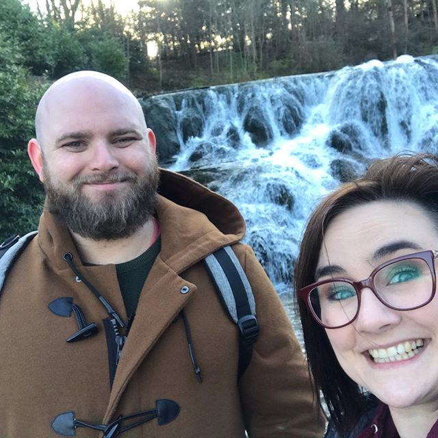 Laura and Will Duggan grinning by a waterfall